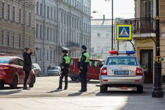 Russian patrol police car and two cops talking to a woman. St. Petersburg, Russia - May 01, 2019: Female police officer  talking to a woman. Russian patrol stock image