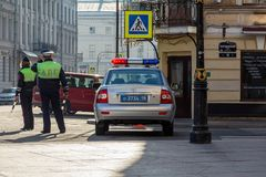 Russian patrol police car and two cops. St. Petersburg, Russia - May 01, 2019: man and woman cops on the street. Russian patrol police car on a city  street royalty free stock image