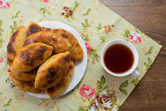 Russian patties with cabbage on a dish  and a cup of tea on the Royalty Free Stock Photos