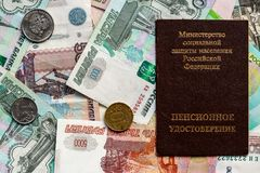 Russian pension certificate and currency. Banknotes and coins. Russian translation - Ministry of Social Protection of Population of Russian Federation. Pension royalty free stock photo