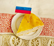 Russian pie. One piece of Russian pie with fish lying on a plate with a patriotic flag Royalty Free Stock Image
