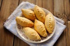 Russian pirogi, small pies on blue linen Stock Photography
