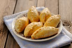 Russian pirogi, small pies on blue linen Royalty Free Stock Image