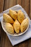 Russian pirogi, small pies on blue linen Stock Photos