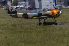 Russian Plane Yak-52. Old propeller piston engine russian yak-52 light aircraft and pilot taxing back to hangars Royalty Free Stock Photos