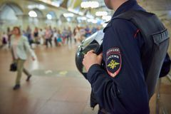 Russian police man in bulletproof vest at metro railway station Komsomolskaya with people in the background. Police is securing pe. Ople and subway property. Man Royalty Free Stock Photography
