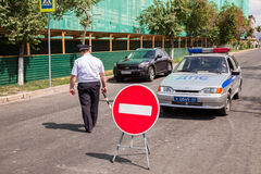 Russian police officer and patrol vehicle parked at the street i Royalty Free Stock Photography