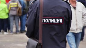 Russian policeman stand on street near going people, Police keeps order at rally. Police keeps order at rally stock video footage
