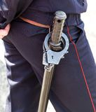 Russian policeman with truncheon and handcuffs. Russian policeman with rubber truncheon and steel handcuffs royalty free stock photography