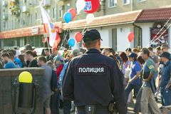 Russian policeman in uniform with a badge on the street at a rally of protest,. View from the back close up royalty free stock photography