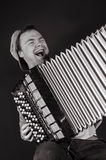 Russian poor man with an accordion. Russian guy playing the accordion and singing a cheerful song stock images