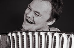 Russian poor man with an accordion. Russian guy playing the accordion and singing a cheerful song royalty free stock photos