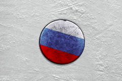 Russian puck on the ice hockey rink. Closeup Stock Photo