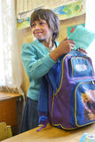 Russian pupil girl junior classes collects schoolbag in rural s. Podol village, Tver region, Russia - May 5, 2006: Junior schoolchildren Nadia Yarunicheva 7 royalty free stock photography