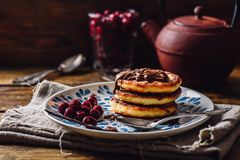 Russian Quark Pancakes. Russian Quark Pancakes with Chocolate Topping and Frozen Cherry. Tea Pot with Spoons and Glass of Berries on Background Royalty Free Stock Images