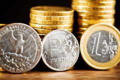 Russian rouble coin between Dollar and Euro Stock Image