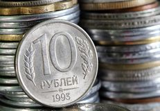 Russian rouble or ruble currency coin with 10. Russian rouble or ruble currency coin with stack of coins piled in the background Royalty Free Stock Images