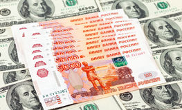 Russian roubles bills laying over dollars Stock Image