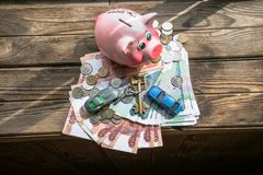 A ray of sunlight on the funny piggy bank and bunch of banknotes and coins on the aged rough wooden windowsill. stock photos