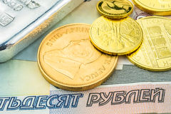 Russian ruble backed by gold and silver. Silver brick and golden coins laying on ruble banknotes Stock Images