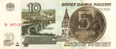 5 russian ruble coin against 10 russian ruble bank note stock photography