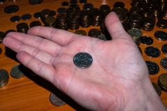 Russian ruble coin in hand on the palm against the background of stacked coins stock images