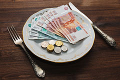 Russian rubles on a plate with silverware. Russian rubles - thousands and five thousands bank notes and different coins on a vintage plate with old silverware stock photo