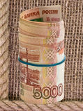 Russian rubles rolled into a tube on a background of burlap Royalty Free Stock Photos