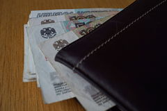 Russian Rubles Russian currency, RUB bank note hanging across a leather wallet. Pile of Russian Rubles Russian currency, RUB bank note hanging across a leather Stock Photo