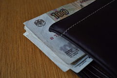 Russian Rubles Russian currency, RUB bank note hanging across a leather wallet Stock Image