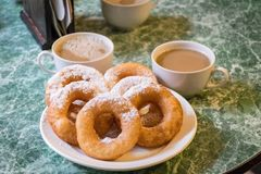 Russian`s donuts serve with icing and hot coffee cups. stock image