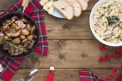 Russian salad and fried potatoes with mushrooms and meat on a wooden table. Delicious traditional winter food in Russia. stock photo
