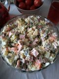 Russian salad from green peas, carrot, boiled potato, boiled sausage, salty pickles, mayonnaise, tasty snack stock images