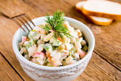 Russian salad olivier. In bowl over wooden table Royalty Free Stock Images