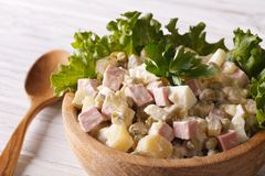 Russian salad Olivier close up in a wooden bowl. horizontal Royalty Free Stock Photography