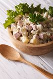 Russian salad Olivier close up in a wooden bowl. Vertical Royalty Free Stock Images