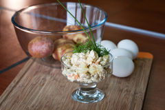Russian salad olivier. Served in the glass with fennel and some ingredients on the background: eggs and potatoes Stock Photo