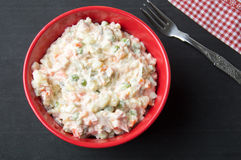 Russian salad in a red bowl Stock Photo