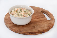 Russian salad served in the bowl on the wooden board Stock Photos
