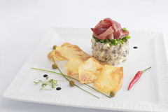Russian salad. Traditional russian salad with fried cheese crisps and ham Stock Photo