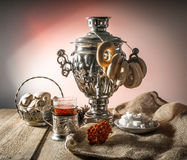 Russian samovar, tea holder, viburnum, cake. On wooden and sackcloth background stock images