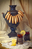 Russian samovar, tea with lemon in faceted glasses with cup holders and bublik. Tinted photo in vintage style Royalty Free Stock Photos