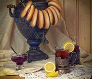 Russian samovar, tea with lemon in faceted glasses with cup holders and bublik. Tinted photo in vintage style Royalty Free Stock Image