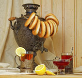 Russian samovar, tea with lemon in faceted glasses with cup holders and bublik. Tinted photo in vintage style Royalty Free Stock Photo