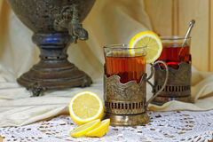 Russian samovar, tea with lemon in faceted glasses with cup holders. Tinted photo in vintage style Stock Photos