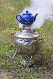 Russian samovar and a teapot. Russian samovar smoking with a blue teapot on it Royalty Free Stock Images