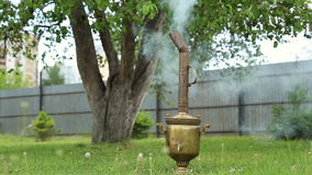 Russian samovar with a tube. Water is heated by burning wood, smoke from the chimney stock video