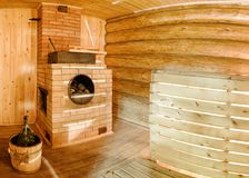 Russian sauna banya. Russian wooden sauna banya with spruce broom and oven with stones Royalty Free Stock Photos