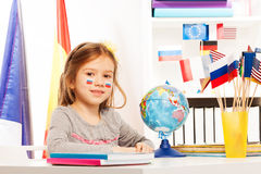 Russian schoolgirl sitting at a desk in classroom. Russian schoolgirl sitting at the desk on geography lesson in the light classroom Royalty Free Stock Photo