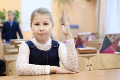 Russian schoolgirl in uniform sitting at the desk in class room and rising hand up. Russia Royalty Free Stock Photos